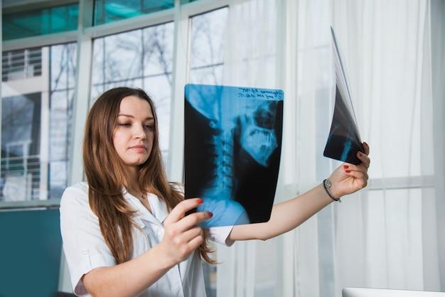 Jonge professionele vrouwelijke arts die röntgenfoto van de patiënt van menselijke schedel onderzoekt tijdens een bezoek. gezondheid geneeskunde concept