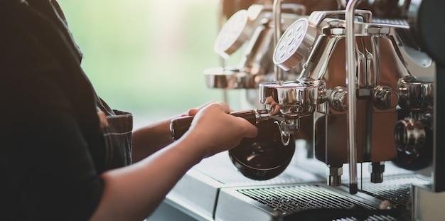 Jonge professionele vrouwelijke barista die koffie met koffiezetapparaatmachine maakt