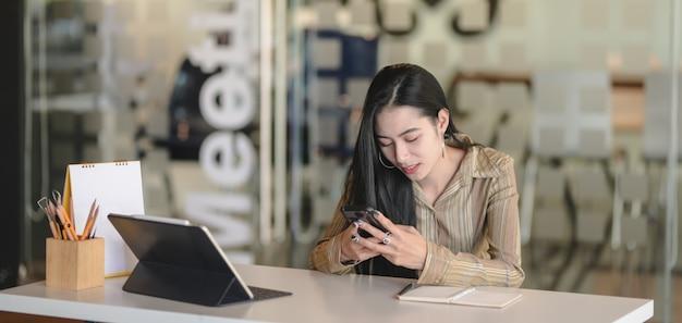 Jonge professionele vrouwelijke ontwerper die aan haar project werkt terwijl het gebruiken van digitale tablet