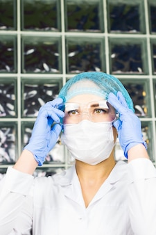 Jonge professionele vrouwelijke wetenschapper die een veiligheidsbril aanpast