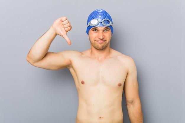 Jonge professionele zwemmer man met een afkeer gebaar, duimen naar beneden.
