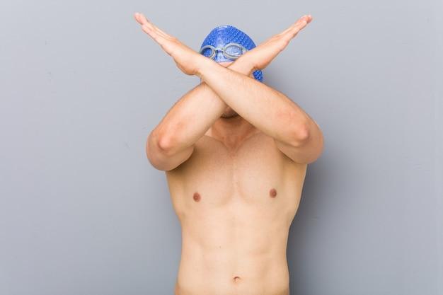Jonge professionele zwemmersmens die twee wapens gekruist houden, ontkenningsconcept.