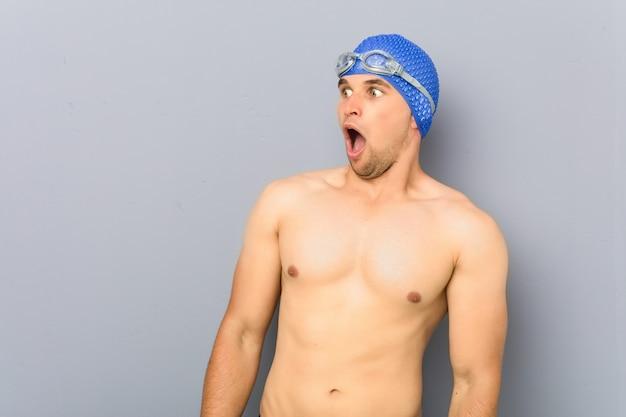 Jonge professionele zwemmersmens die wordt geschokt vanwege iets dat ze heeft gezien.