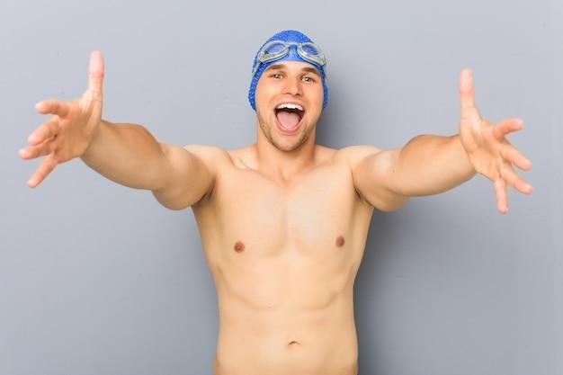 Jonge professionele zwemmersmens voelt zich zelfverzekerd en geeft een knuffel aan de camera.