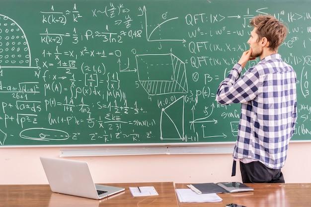 Jonge professor die stelling op een schoolbord bewijst
