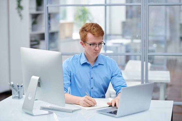 Jonge programmeur kijken door software op laptopvertoning en notities maken zittend door bureau