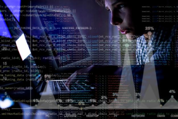 Jonge programmeur voor de laptop schrijft 's nachts een code