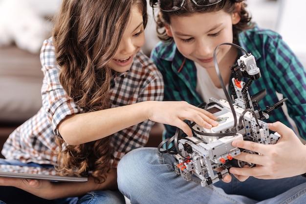 Jonge programmeurs werken samen. slimme behulpzame positieve kinderen die thuis zitten en gadgets en apparaten testen terwijl ze vreugde uiten Premium Foto
