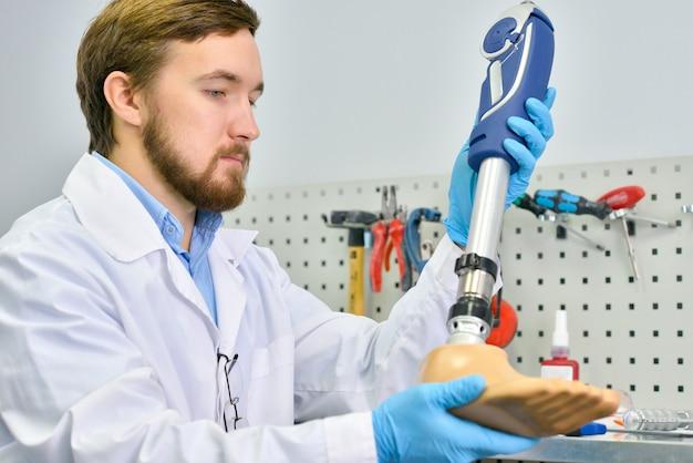 Jonge prosthetist die kunstmatig been houdt