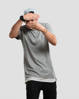 Jonge rapper man kijkt door een gat, verbergt en loensde