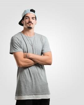 Jonge rapper man kruist zijn armen, serieus en imposant, voelt zich zelfverzekerd en toont kracht