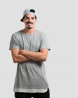 Jonge rapper man overschrijding zijn armen, glimlachend en blij, zelfverzekerd en vriendelijk