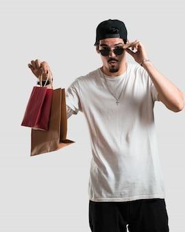 Jonge rapper man vrolijk en lachend, erg enthousiast met boodschappentassen, klaar om te gaan winkelen en op zoek naar nieuwe aanbiedingen