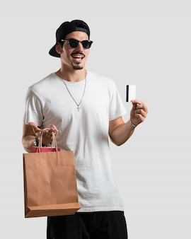 Jonge rapper man vrolijk en lachend, erg enthousiast met de nieuwe bankkaart en boodschappentassen, klaar om te gaan winkelen