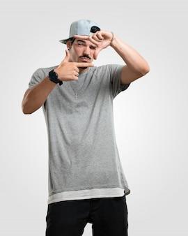 Jonge rapperman die een kadervorm met handen maakt, die probeert te concentreren alsof het een camera was