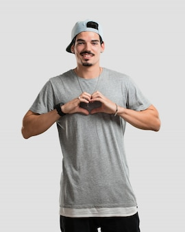 Jonge rappermens die een hart met handen maakt, die het concept liefde en vriendschap uitdrukken, gelukkig en glimlachend