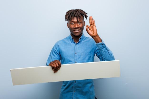 Jonge rasta zwarte man die een aanplakbiljet houdt, vrolijk en vol vertrouwen die ok gebaar toont.
