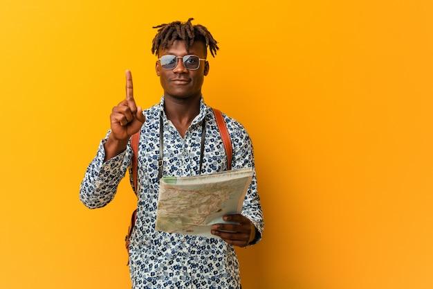 Jonge rasta zwarte man met een kaart met nummer één met vinger.