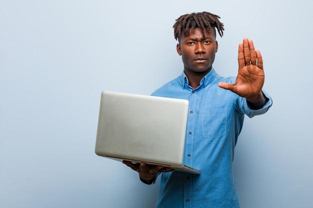 Jonge rasta zwarte man met een laptop staan met uitgestrekte hand met stopbord, waardoor u wordt voorkomen.