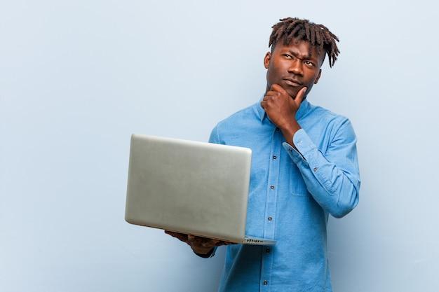 Jonge rasta zwarte man met een laptop zijwaarts op zoek met twijfelachtige en sceptische uitdrukking.