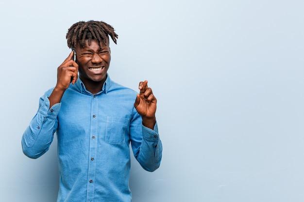 Jonge rasta zwarte man met een telefoon kruising vingers voor het hebben van geluk