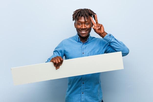 Jonge rasta zwarte mens die een aanplakbiljet houdt die overwinningsteken toont en breed glimlacht.