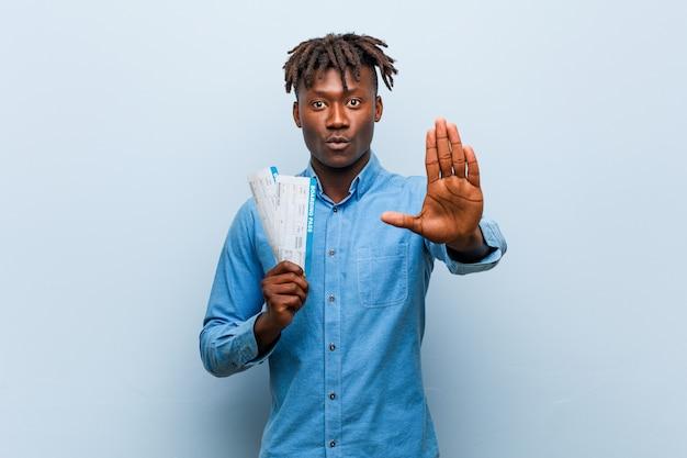 Jonge rasta zwarte mens die luchtkaartjes houden die zich met uitgestrekte hand bevinden die eindeteken tonen, die u verhinderen.