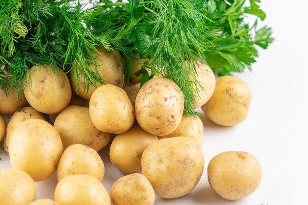 Jonge rauwe aardappelen en verse greens geïsoleerd op een witte achtergrond close-up