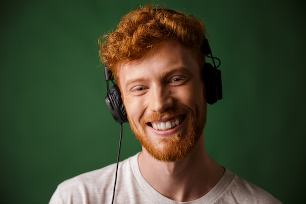 Jonge readheadmens het luisteren muziek in hoofdtelefoons