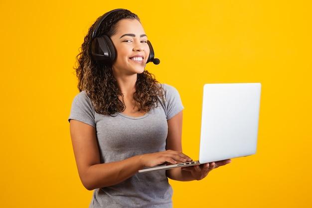 Jonge receptionistevrouw die met notitieboekje en hoofdtelefoon werkt.
