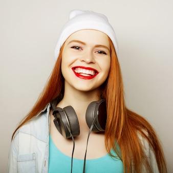 Jonge redhairvrouw met hoofdtelefoons het luisteren muziek.