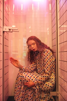 Jonge redhead krullende vrouw in koffie bij latrine bij douche