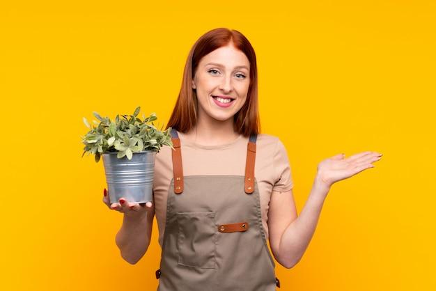 Jonge redhead tuinmanvrouw die een installatie over geïsoleerde gele holding houden copyspace denkbeeldig op de palm