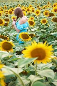 Jonge redhead vrouw met gevlochten kapsel in zomer zonnebloem veld