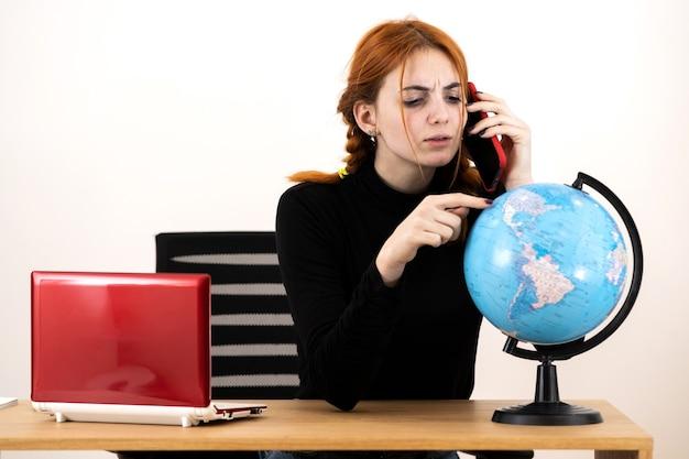 Jonge reisagent vrouw zit achter bureau met laptopcomputer en geografische wereldbol praten op een mobiele telefoon.