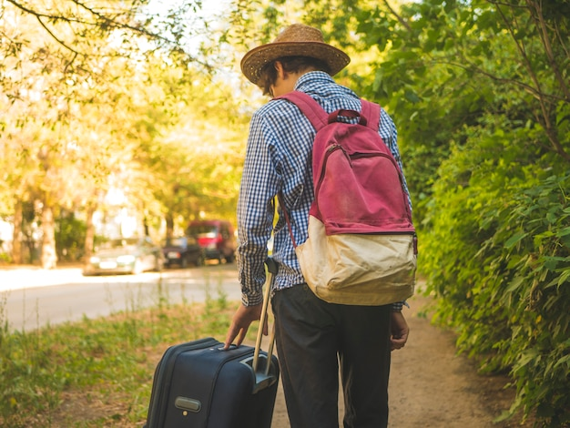 Jonge reizende man met rugzak en koffer die in de stadsstraat lopen