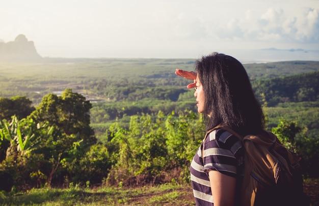 Jonge reiziger backpacker kijkt uit naar de zon om het landschap te bekijken