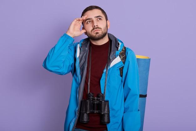 Jonge reiziger blanke man opzoeken met twijfelachtige gezichtsuitdrukking