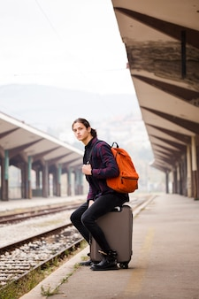 Jonge reiziger die bij het station wacht