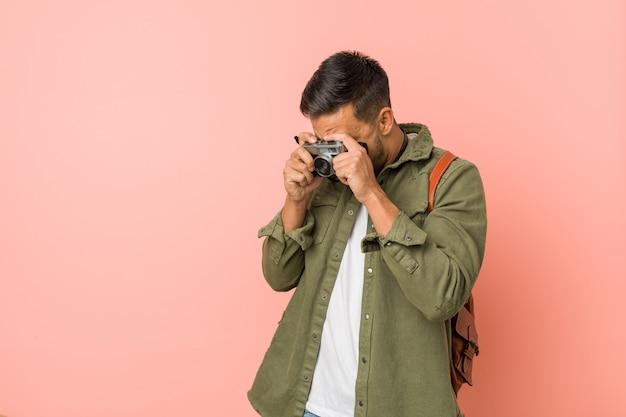 Jonge reiziger die foto's met een retro camera neemt.