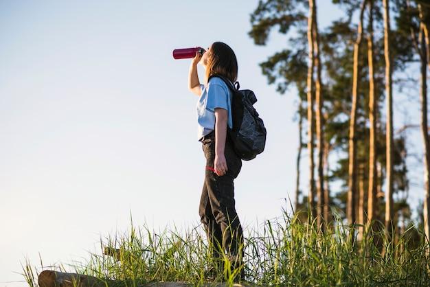 Jonge reiziger die van thermosflessen drinkt