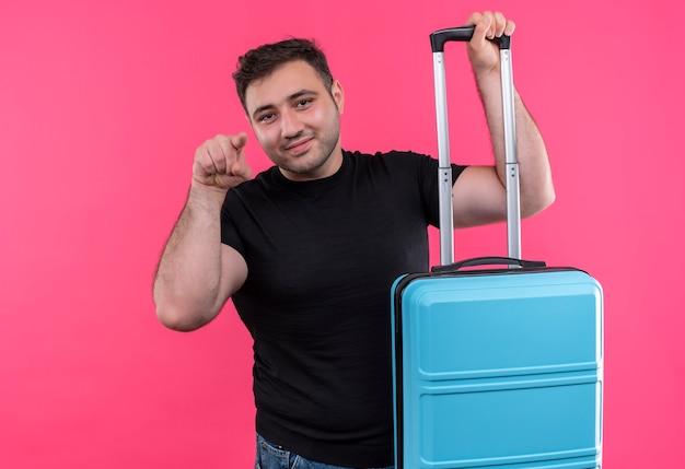 Jonge reiziger in zwarte t-shirt met koffer blij en positief wijzend met wijsvinger, glimlachend en staande over roze muur