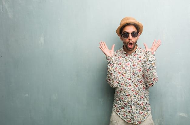 Jonge reiziger man draagt een kleurrijke shirt gek en wanhopig, schreeuwen uit de hand