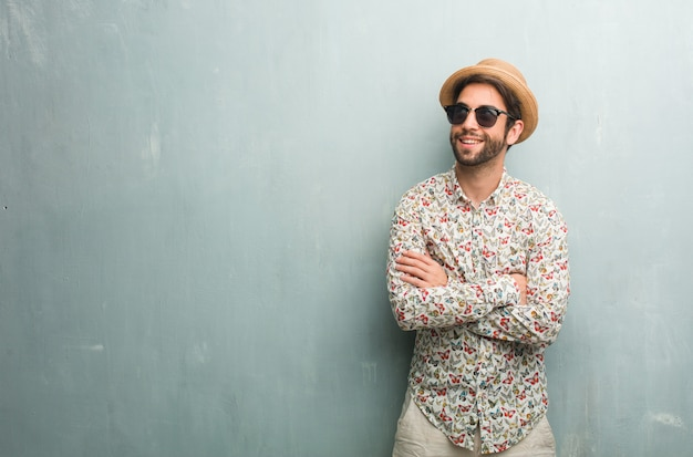 Jonge reiziger man draagt een kleurrijke shirt opzoeken, denken aan iets leuks en een idee hebben