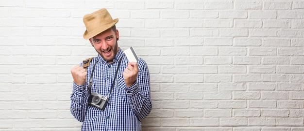 Jonge reiziger man draagt rugzak en een vintage camera erg blij en opgewonden, het verhogen van de armen, het vieren van een overwinning of succes, het winnen van de loterij. een creditcard hebben.