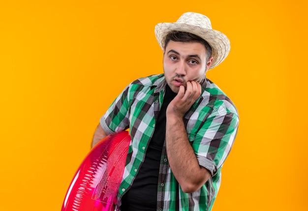 Jonge reiziger man in geruit overhemd en zomerhoed met opblaasbare ring bezorgd en nerveus nagels bijten staande over oranje muur