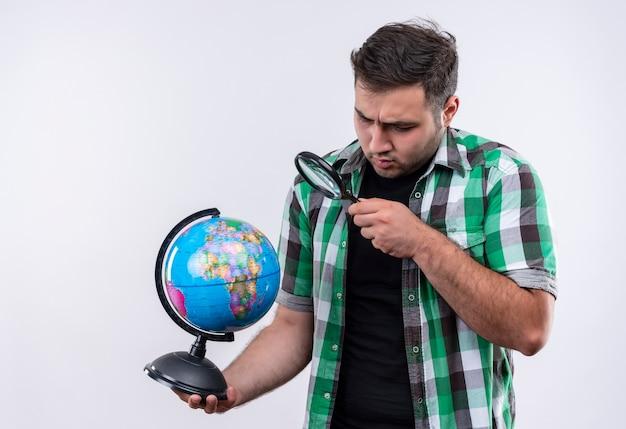 Jonge reiziger man in ingecheckte overhemd bedrijf globe kijken door vergrootglas kijken verbaasd staande over witte muur