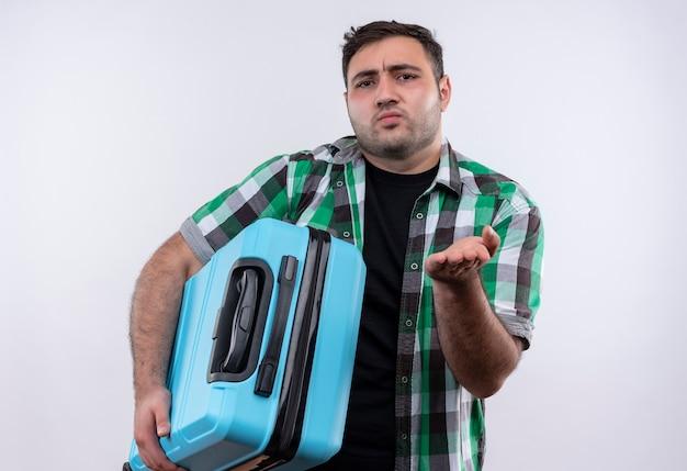 Jonge reiziger man in ingecheckte overhemd met koffer op zoek verward opheffende arm als het stellen van vraag staande over witte muur