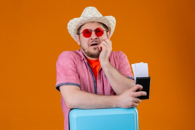 Jonge reiziger man in zomer hoed zonnebril houden koffer en vliegtickets kijken camera gestrest en nerveus staande over oranje achtergrond