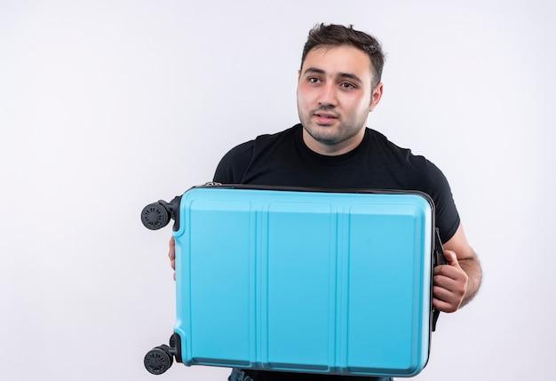 Jonge reiziger man in zwarte t-shirt bedrijf koffer opzij kijken verbaasd staande over witte muur
